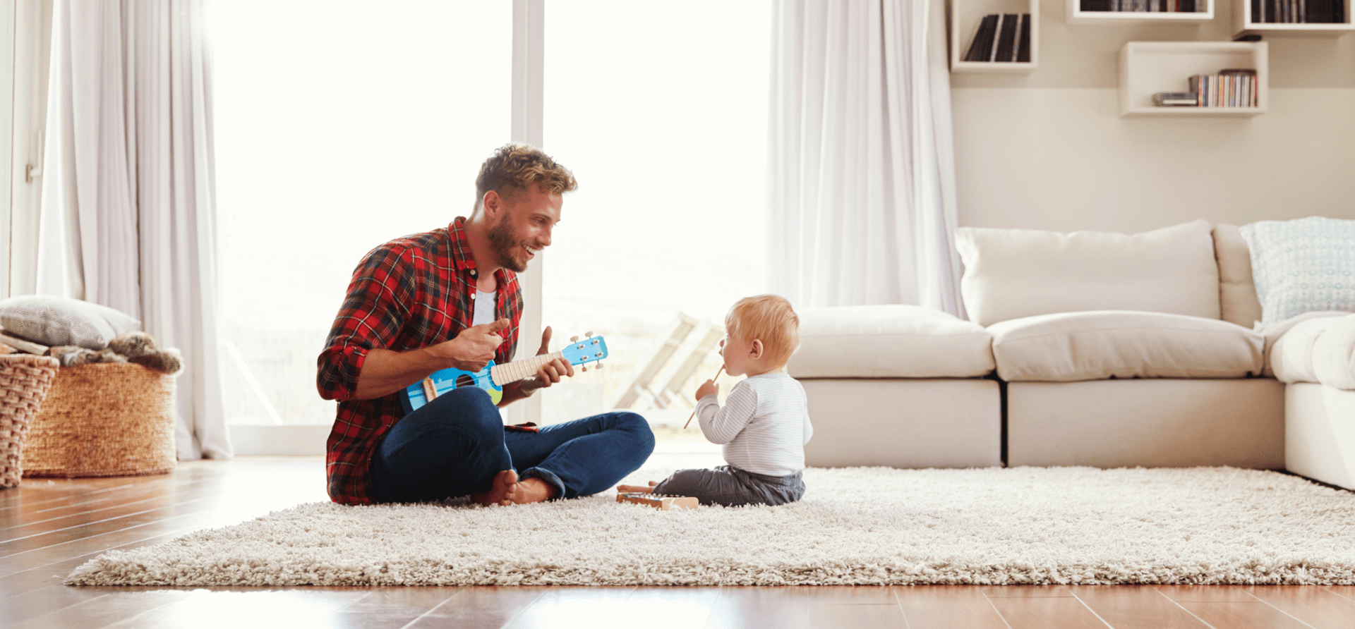 Dad smiling as he plays with young toddler's toy guitar, toddler looks up at him in a light and airy room